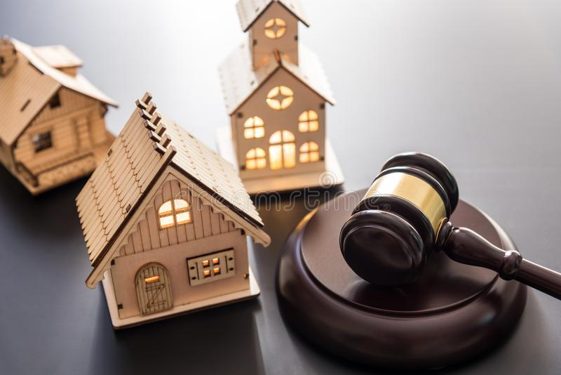 De hamer van de hamerrechtvaardigheid en houten huis op zwarte achtergrond stock afbeeldingen