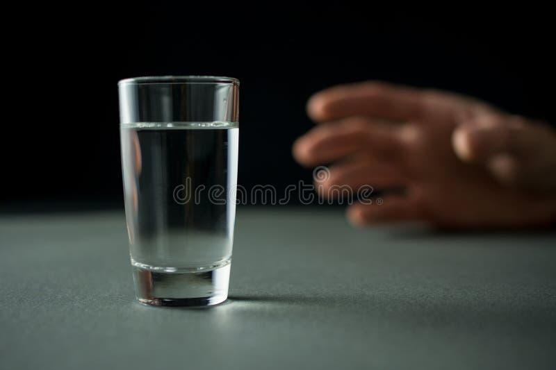 De hand bereikt voor een glas van wodka of alcoholdrank stock foto's