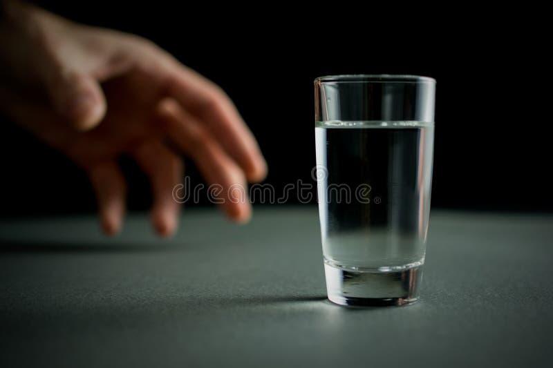 De hand bereikt voor een glas wodka royalty-vrije stock afbeelding