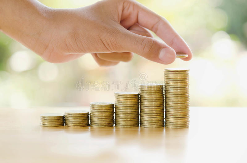 de hand bespaart geld met het muntstuk van het stapelgeld voor het kweken van grafiek uw bus royalty-vrije stock foto's