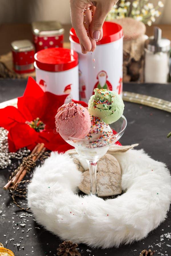 De hand bestrooit decoratie op aardbei, vanille en pistacheroomijs op Kerstmisachtergrond stock foto's