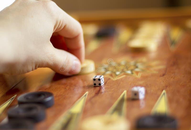 De hand beweegt witte controleurs in de backgammonpartij stock afbeeldingen
