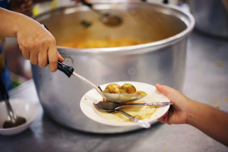 De hand bood aan om voedsel van een rijke manaandeel te schenken: Het voeden Concepten stock foto