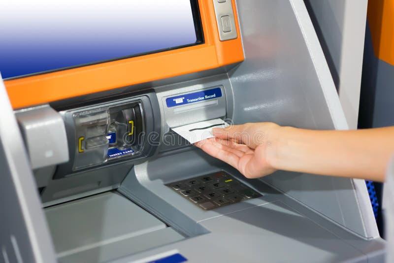 De hand die ATM-kaart opnemen in bankmachine voor trekt geld terug royalty-vrije stock foto