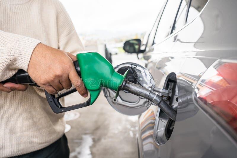 De hand die de auto met brandstof opnieuw vullen bij tankt post bij Grijze auto bij benzinestation die met brandstof in Nieuw Zee stock foto's