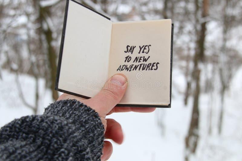 De hand die een boek met de inschrijving houden zegt ja aan nieuwe avonturen op de achtergrond van het de winterbos royalty-vrije stock foto's