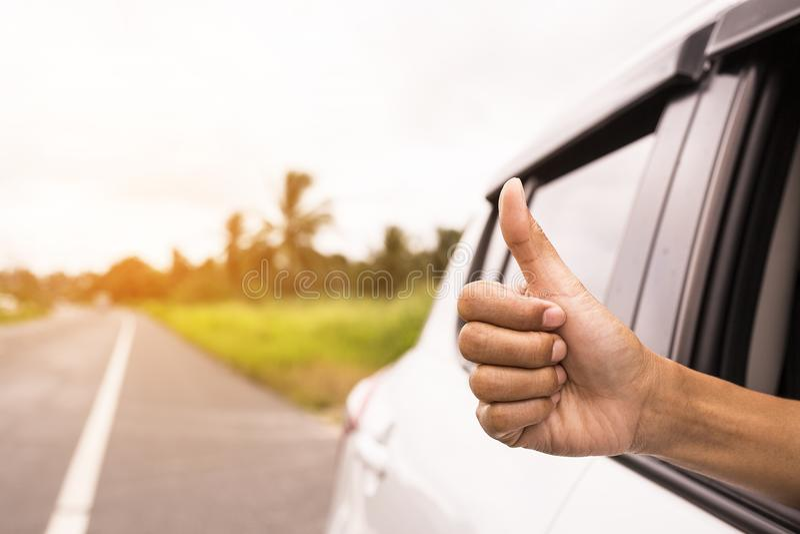 De hand die een duimenteken geven werpt omhoog het venster van een auto parkeerde dichtbij de wegen Het symbool van een hand voor royalty-vrije stock foto