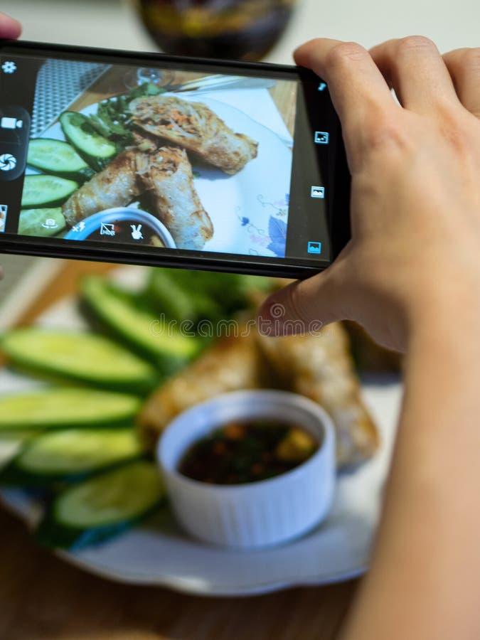 De hand die een smartphone gebruiken aan foto braadde Vietnamese pannekoeken royalty-vrije stock fotografie