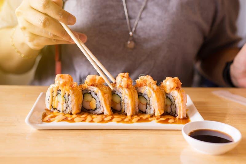 De hand die eetstokjessushi gebruiken rolt op schotel met de saus van Shoyu Japan in restaurant royalty-vrije stock foto
