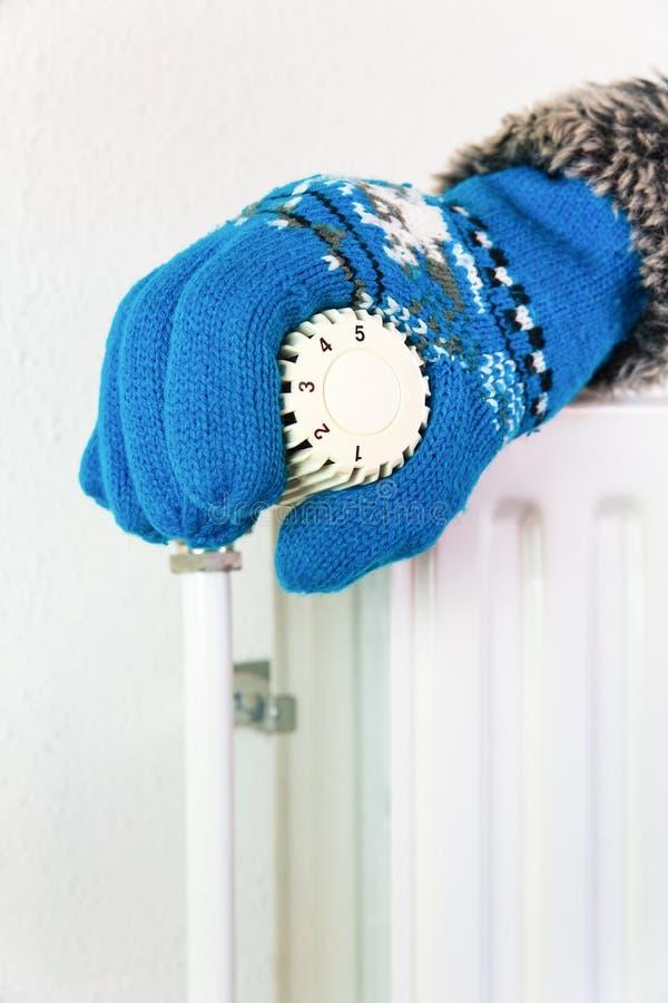De hand die handschoen dragen draait het verwarmen klep in de winter royalty-vrije stock fotografie