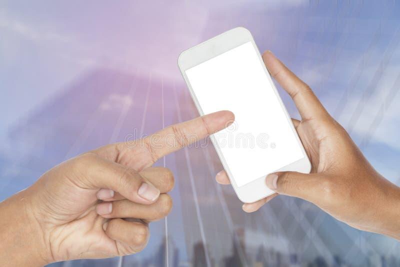 De hand die moderne slimme telefoon met samenvatting houden vertroebelde motie van de moderne glasbouw royalty-vrije stock afbeeldingen