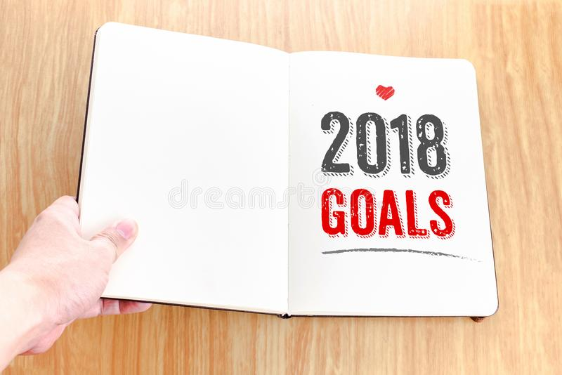 De hand die open notitieboekje met 2018 doelstellingen houden legt het op houten tabl royalty-vrije stock foto