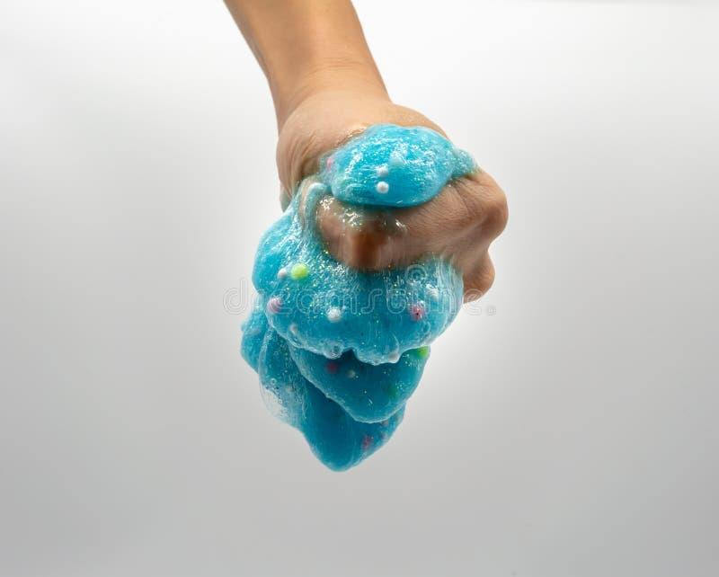 De hand die transparant blauw spelen schittert slijm op wit royalty-vrije stock afbeelding