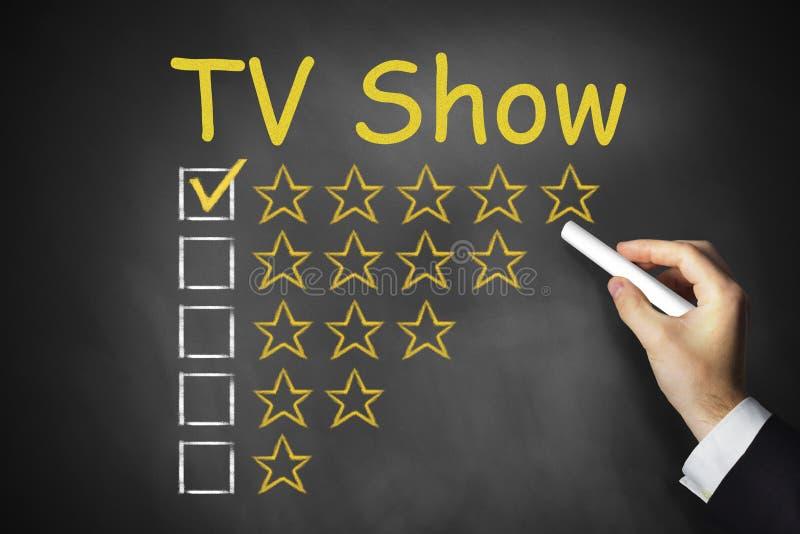 De hand die TV schrijft toont op zwart bord stock afbeeldingen