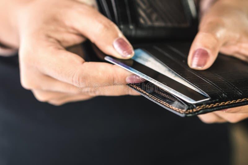 De hand die van de close-upvrouw creditcard van zwarte beurs nemen royalty-vrije stock fotografie
