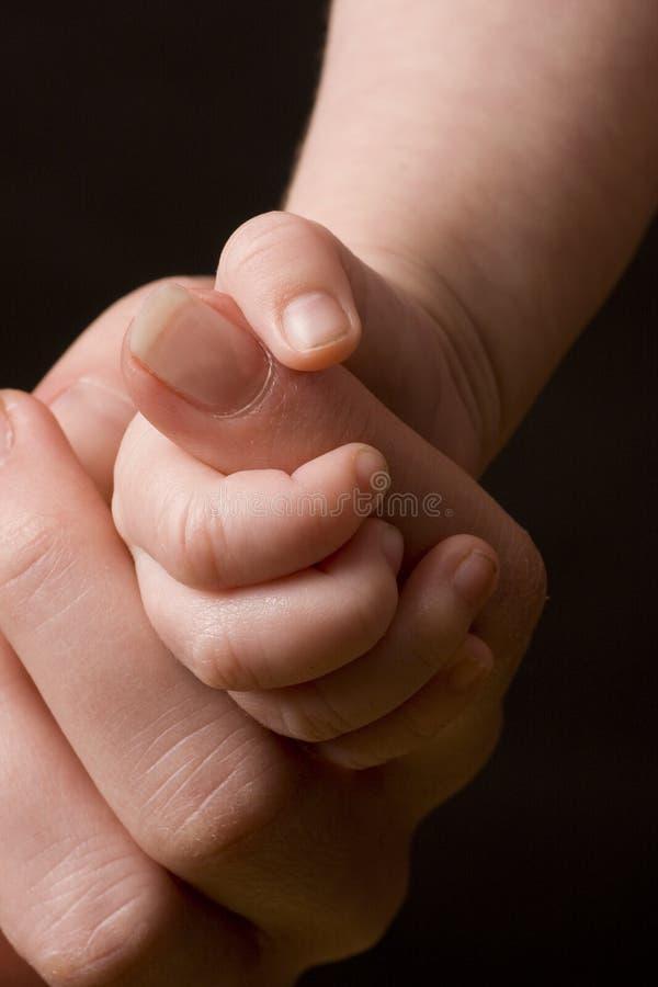 De hand die van de baby volwassen vinger grijpt stock foto