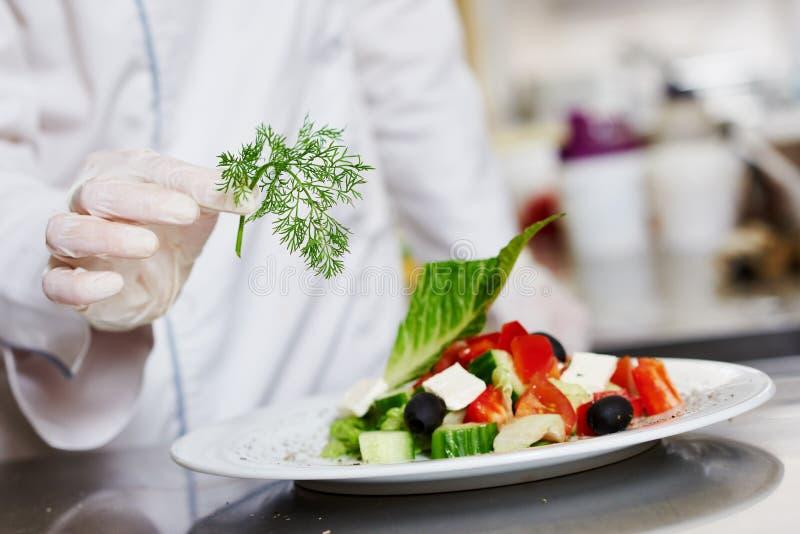 De hand die van de kokchef-kok voorbereid saladevoedsel verfraaien royalty-vrije stock afbeelding