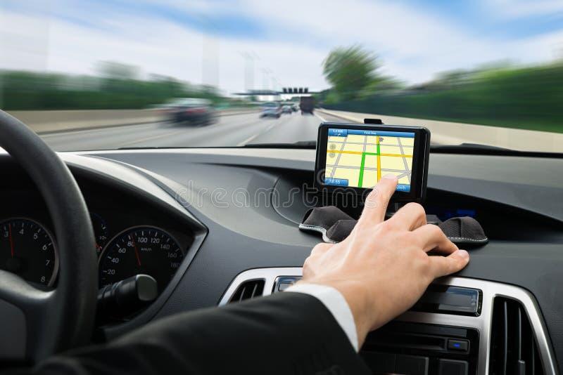 De hand die van de persoon gps navigatiesysteem in auto met behulp van stock fotografie
