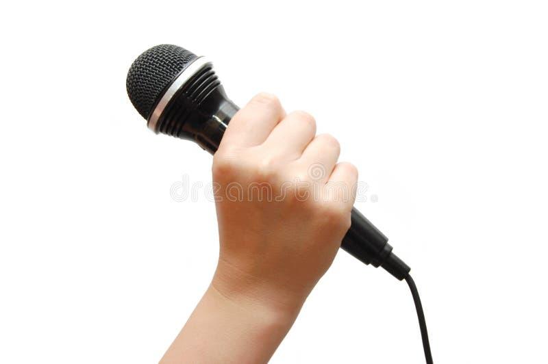 De hand die van de vrouw een microfoon houdt stock foto's