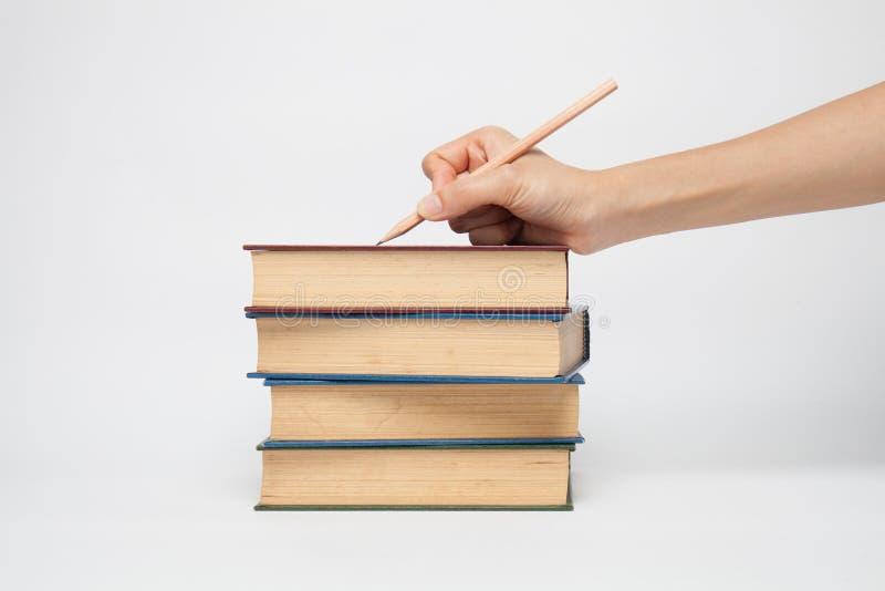 De hand die van de vrouw een potlood op een witte witte achtergrond houden stock fotografie