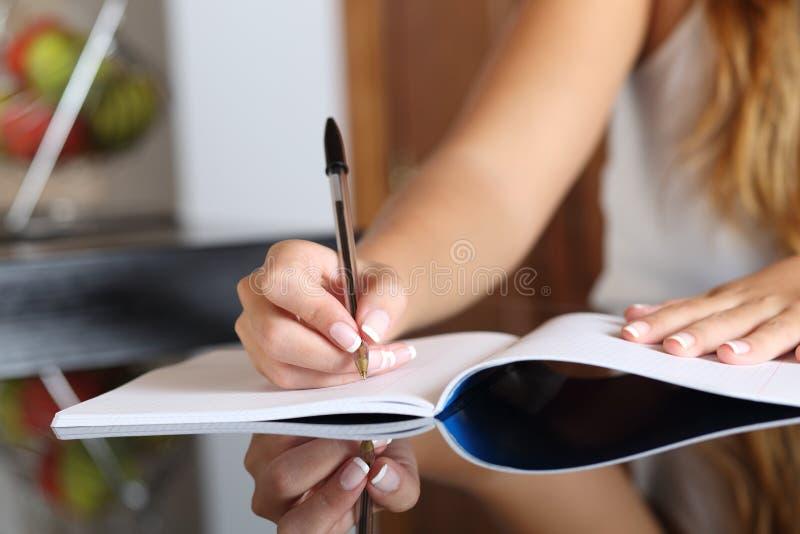 De hand die van de vrouwenschrijver in een notitieboekje thuis schrijven stock afbeeldingen