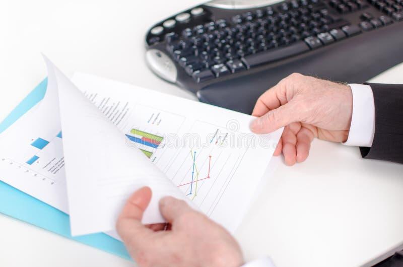 De hand die van de zakenman een document houdt stock fotografie