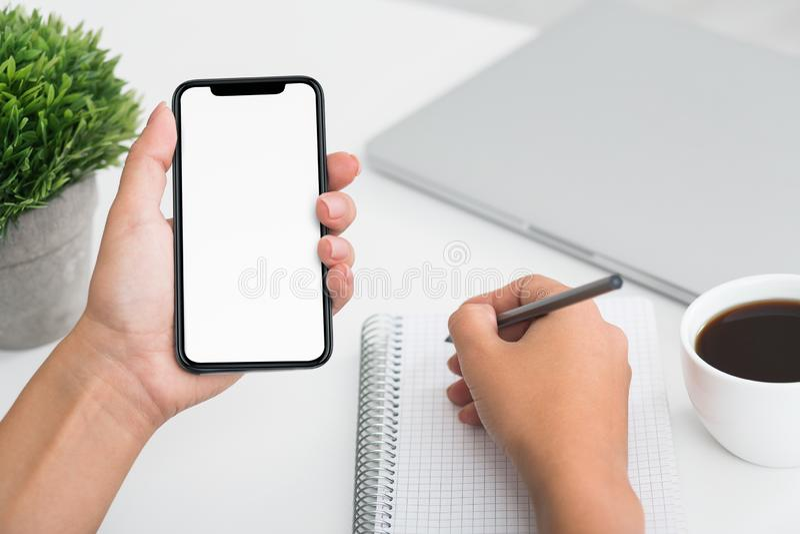 De hand die van de Fmalestudent op notitieboekje schrijven en smartphone gebruiken royalty-vrije stock foto's