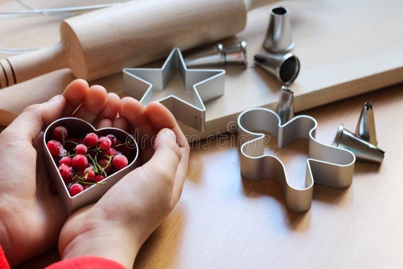 De hand die van het meisje traditionele feestelijke koekjes maken Het bakken met liefdeconcept Moederdag, de Dag van Vrouwen, de  royalty-vrije stock fotografie