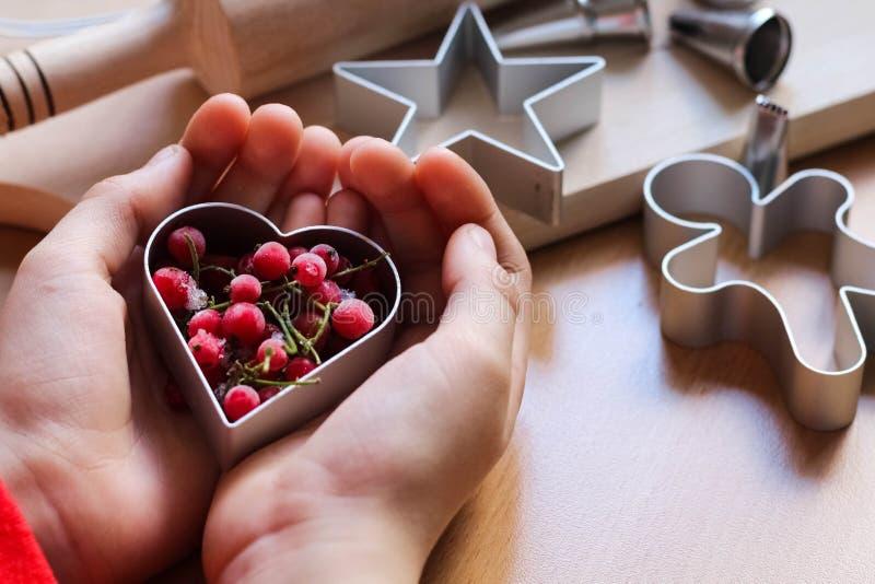 De hand die van het meisje traditionele feestelijke koekjes maken Het bakken met liefdeconcept Moederdag, de Dag van Vrouwen, de  royalty-vrije stock afbeeldingen