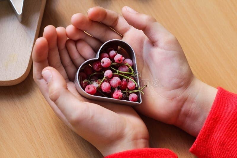 De hand die van het meisje traditionele feestelijke koekjes maken Het bakken met liefdeconcept Moederdag, de Dag van Vrouwen, de  stock afbeelding