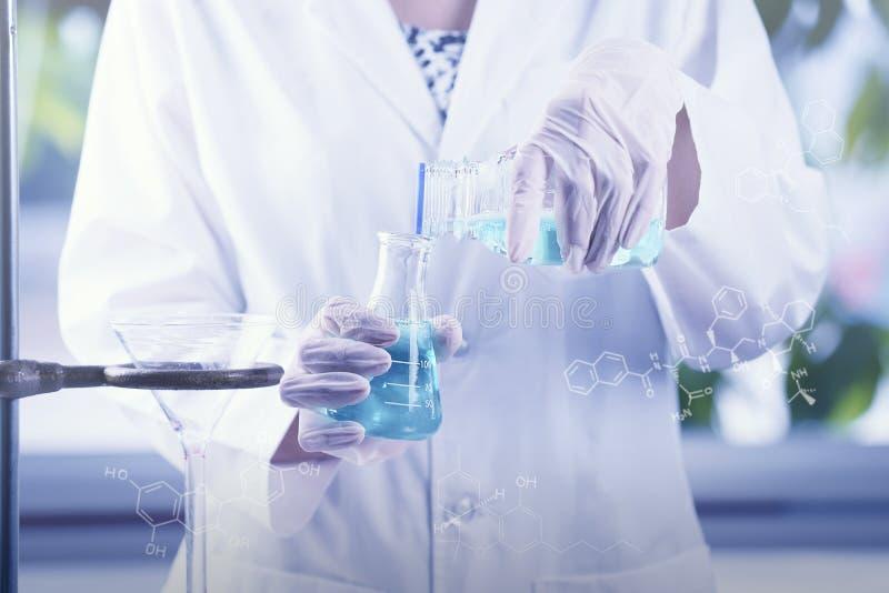 De hand die van de onderzoekerswetenschapper reageerbuizen controleren, latend vallen vloeistof stock afbeelding