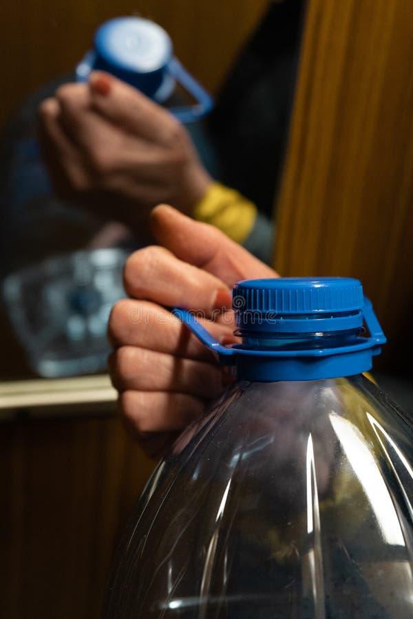 De hand die van de oudere hogere vrouw een grote blauwe plastic fles in een lift houden royalty-vrije stock foto
