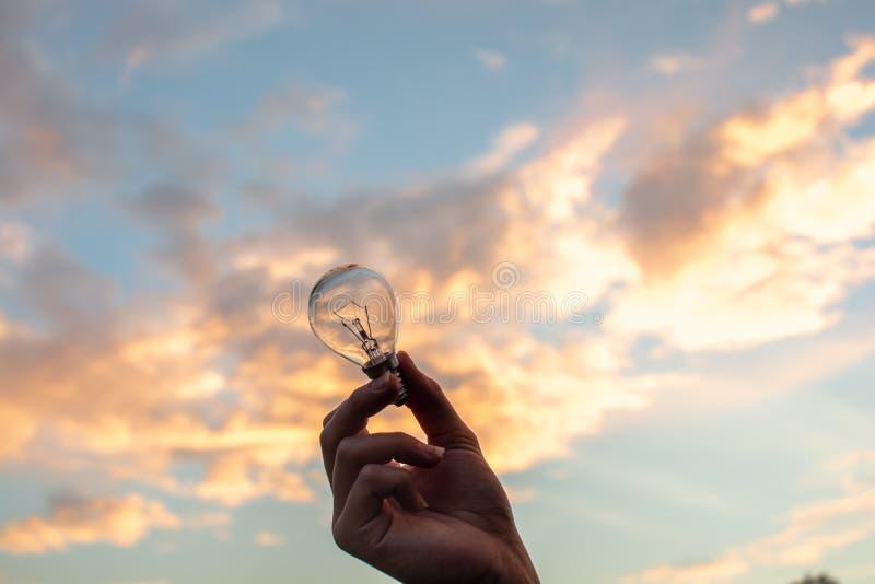De hand die van de persoon een kleine lightbulb op een mooie witte bewolkte hemel op de achtergrond steunen stock afbeeldingen