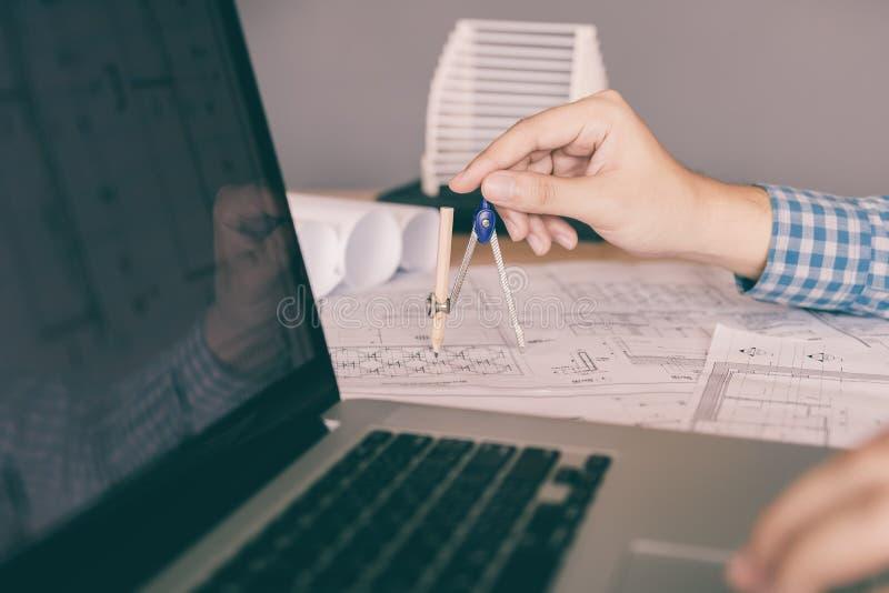 De hand die van de techniekmens op blauwdruk trekken en laptop met behulp van stock foto's