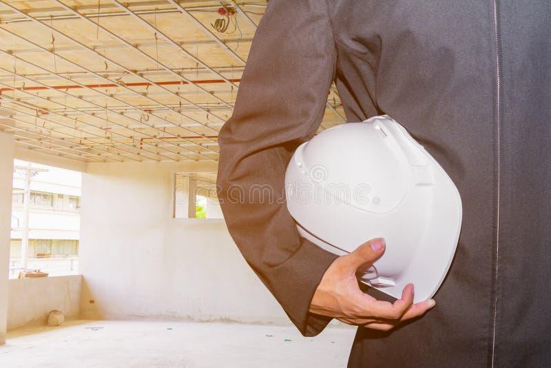 De hand die van de techniekzakenman witte de bouwwerf van de veiligheidshoed binnenlandse de bouwhuisvesting houden stock foto