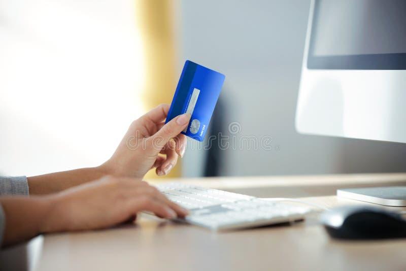 De hand die van de vrouw blauwe creditcard voor thuis het winkelen online met computer houden stock foto's