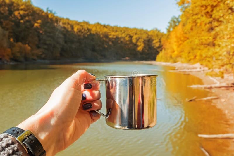 De hand die van de vrouw een mok met hete thee houden dichtbij het meer in een warme zonnige de herfstdag stock fotografie