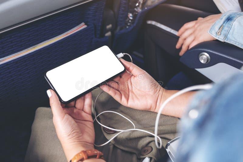 De hand die van de vrouw een zwarte smartphone met het lege Desktopscherm en oortelefoon in cabine houden royalty-vrije stock afbeeldingen