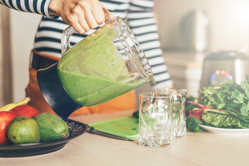 De hand die van de vrouw groene smoothie gieten in een glas stock foto's