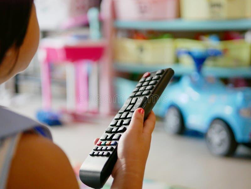 De hand die van weinig Aziatische baby een televisieafstandsbediening houden, terwijl thuis het letten van op het royalty-vrije stock fotografie