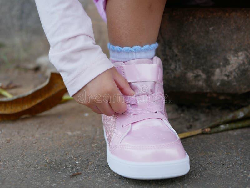 De hand die van weinig babymeisje schoenveter proberen zelf te schikken stock foto