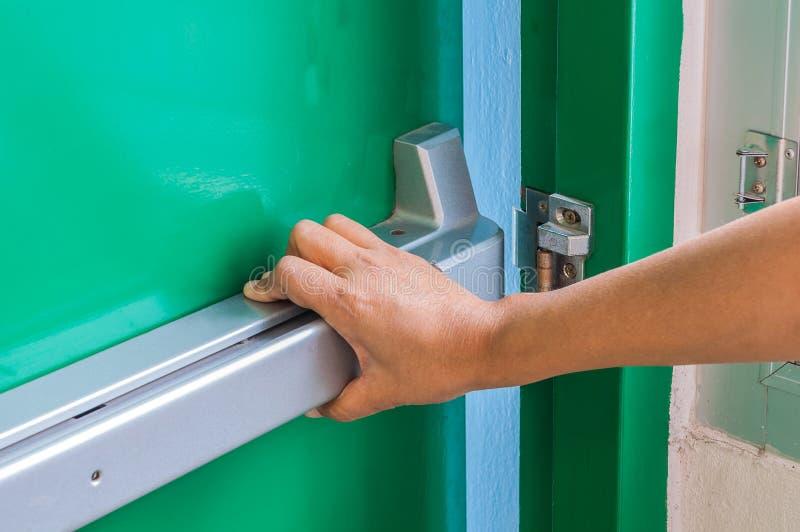 De hand duwt/opent de deur van de noodsituatienooduitgang stock foto's