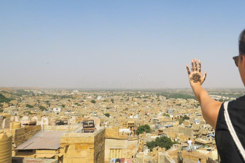 De hand en het panorama van de hennatatoegering over de Indische woestijnstad Jaisalmer royalty-vrije stock afbeelding