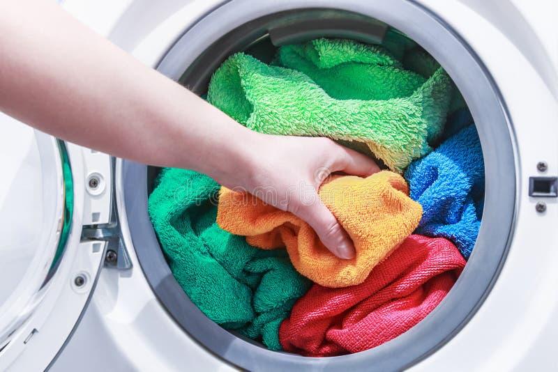 De hand en zet de wasserij in de wasmachine stock afbeelding