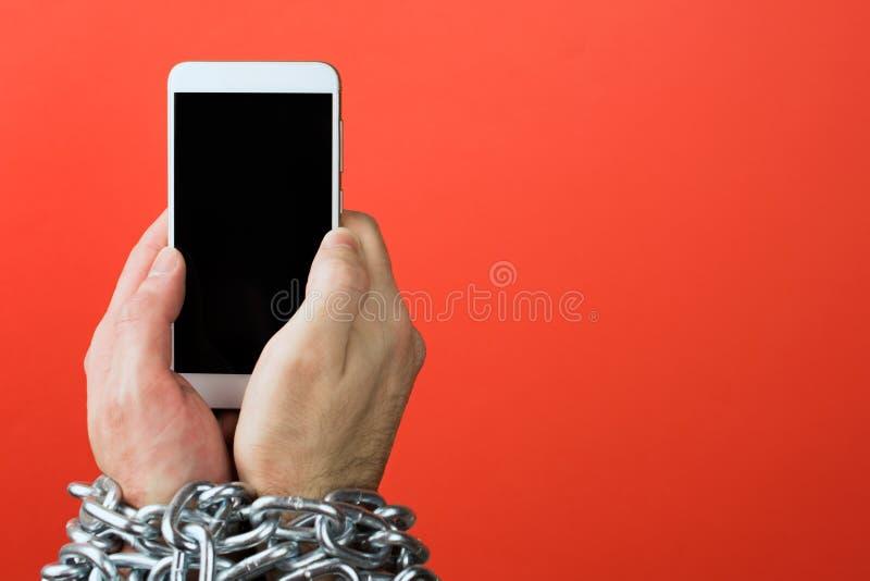 De hand is gebonden met een ketting aan smartphone royalty-vrije stock afbeeldingen