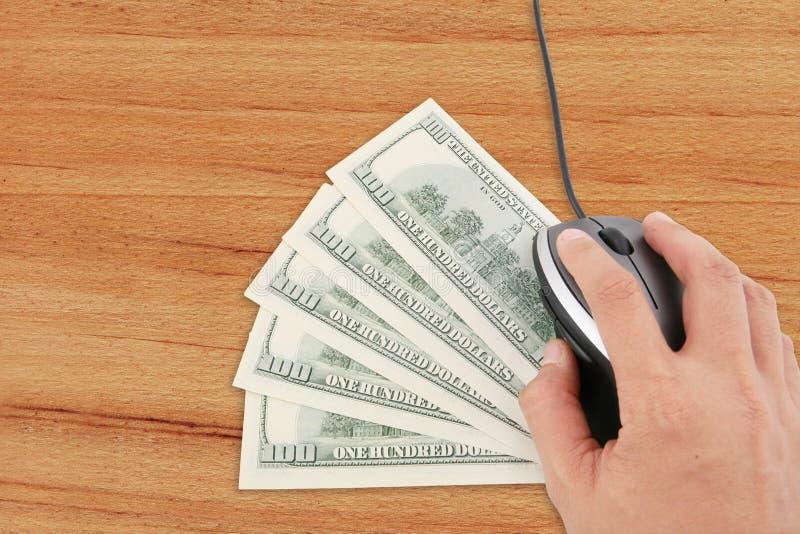 De hand gebruikt computermuis met geld op bureau royalty-vrije stock afbeeldingen