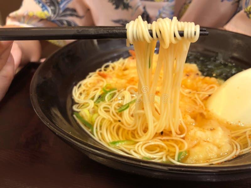 De hand gebruikt eetstokjes aan bestelwagen Tempura ramen in de zwarte plaat, traditioneel Japans voedsel royalty-vrije stock foto's