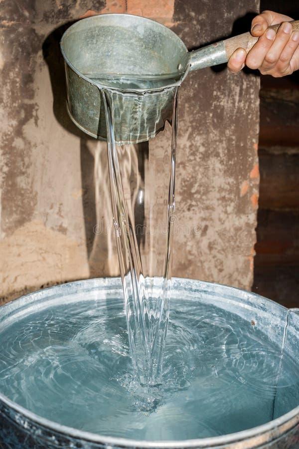 De hand giet water van emmer in de metaalpot in landelijke bathhouse royalty-vrije stock afbeeldingen