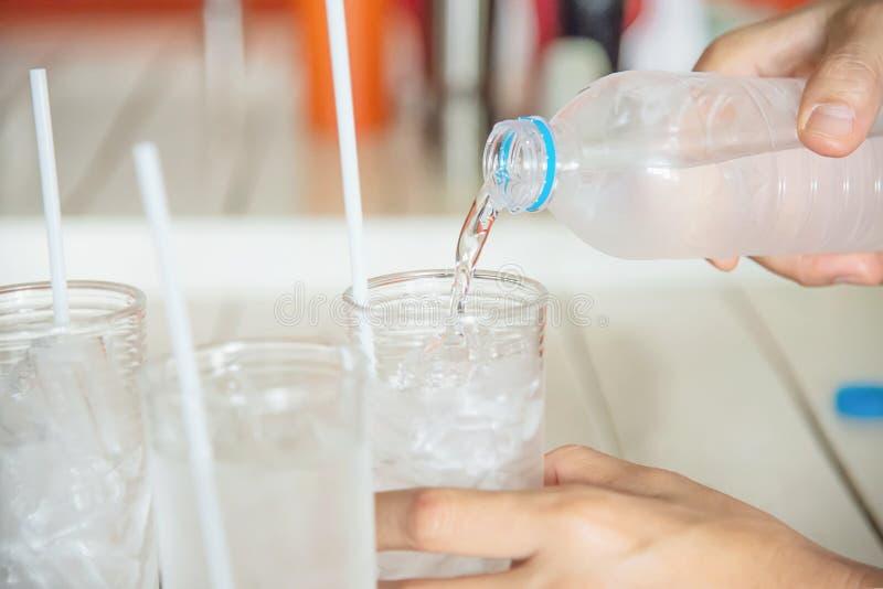 De hand giet zoet water in een glas met ijs royalty-vrije stock foto