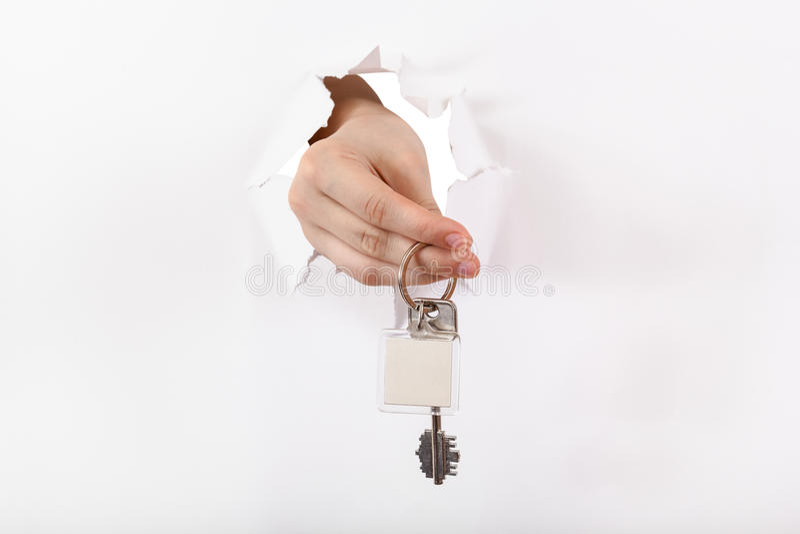 De hand houdt de sleutelring door een gat stock fotografie